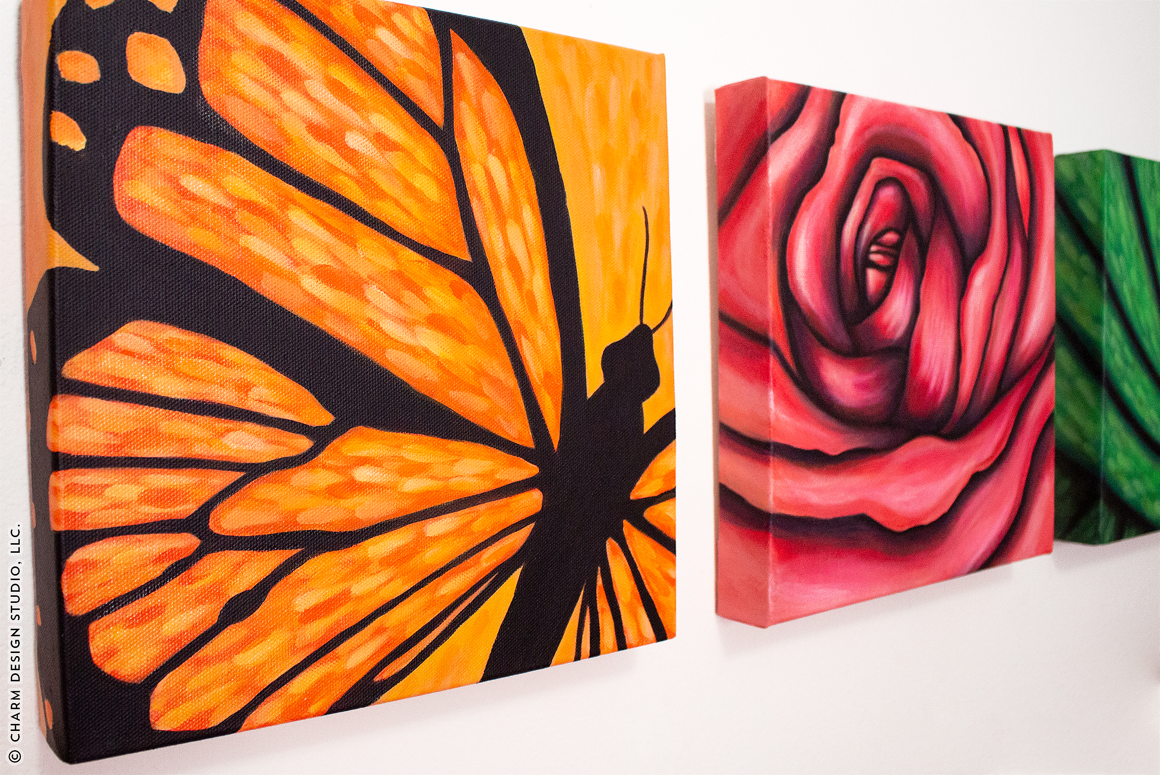 finished acrylic paintings on canvas hung up on wall | image © Charm Design Studio, LLC.